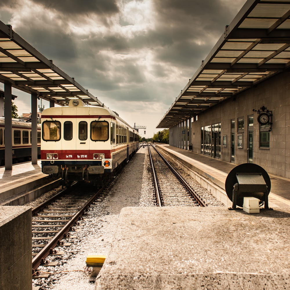 photo of white and red train station under grey cloudy sky