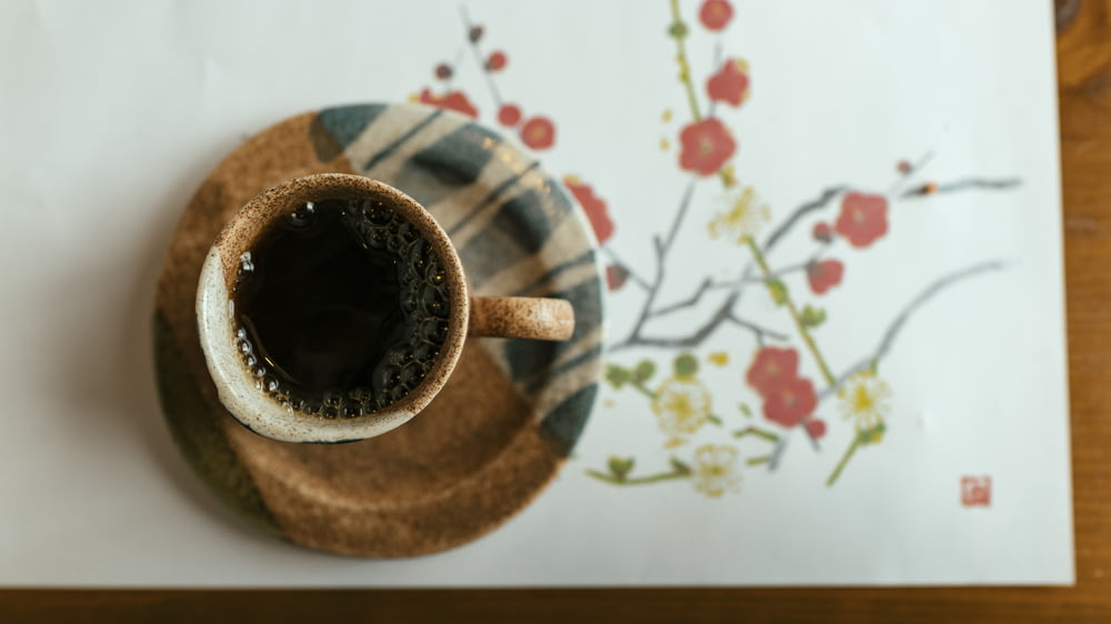 brown and white mug filled with coffee on saucer