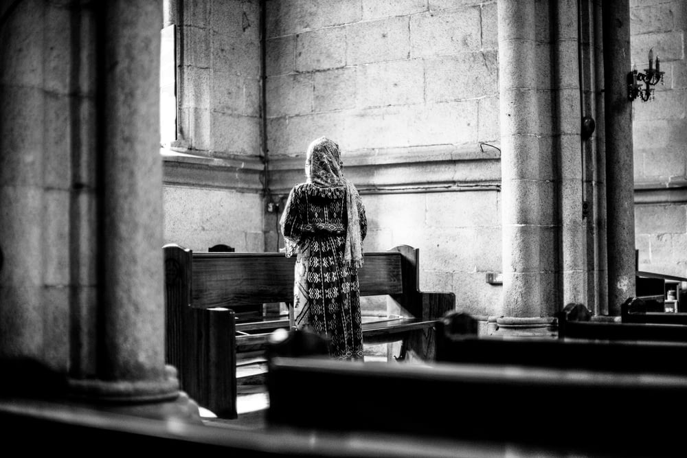 grayscale photo of person standing in front of pew bench