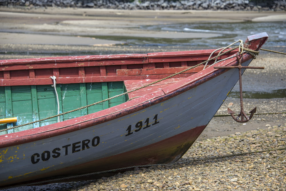 white and red Costero 1911 boat at shore