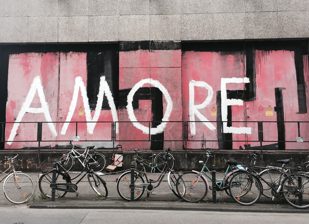 gray and black bicycles in front of Amore graffiti