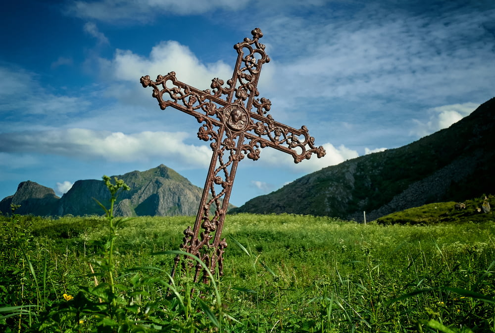 leaning brown metal cross on green grass field near mountains at daytime