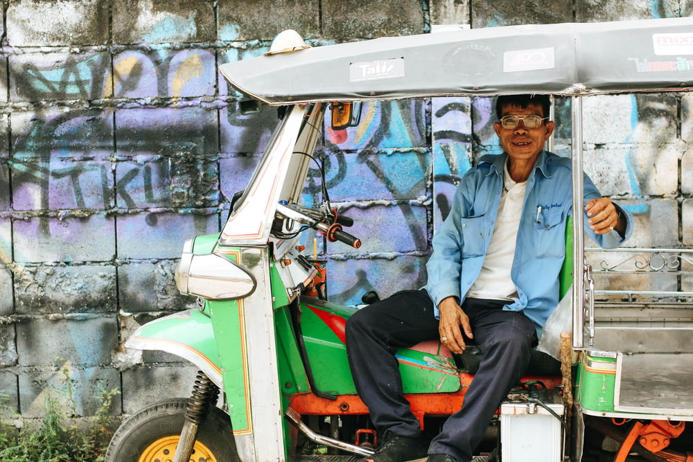 man sitting on auto rickshaw near graffiti wall during daytime