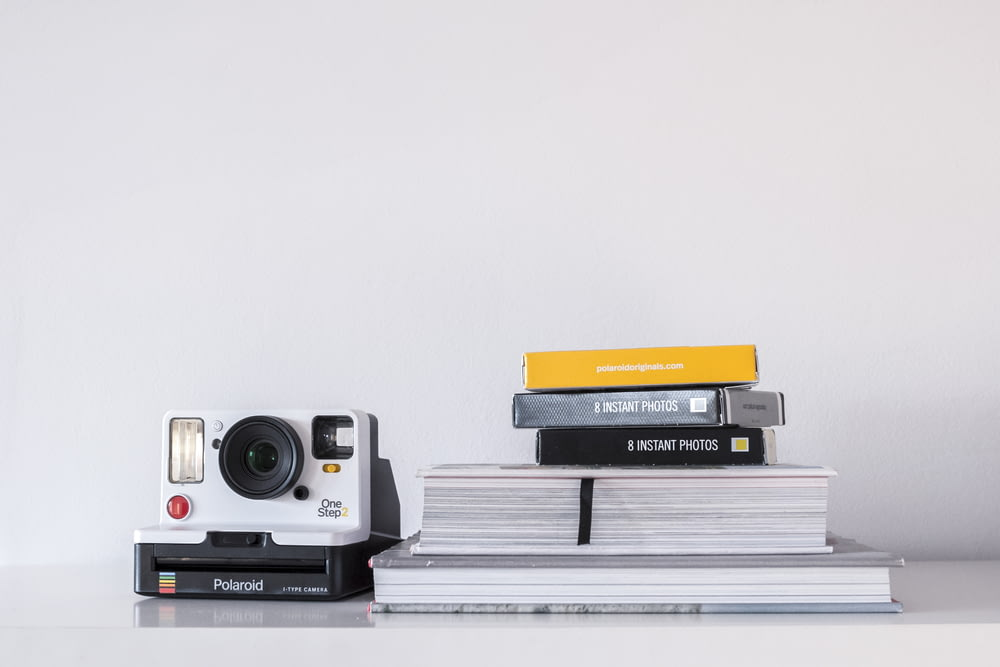 white and black Polaroid instant camera beside book