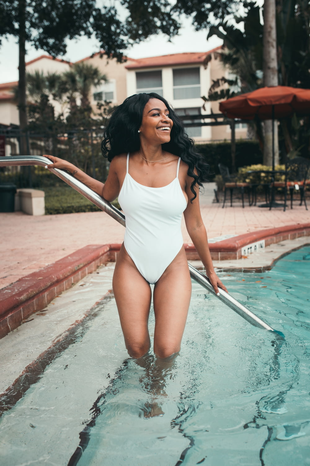 woman wearing white spaghetti strap one-piece swimsuit in poon