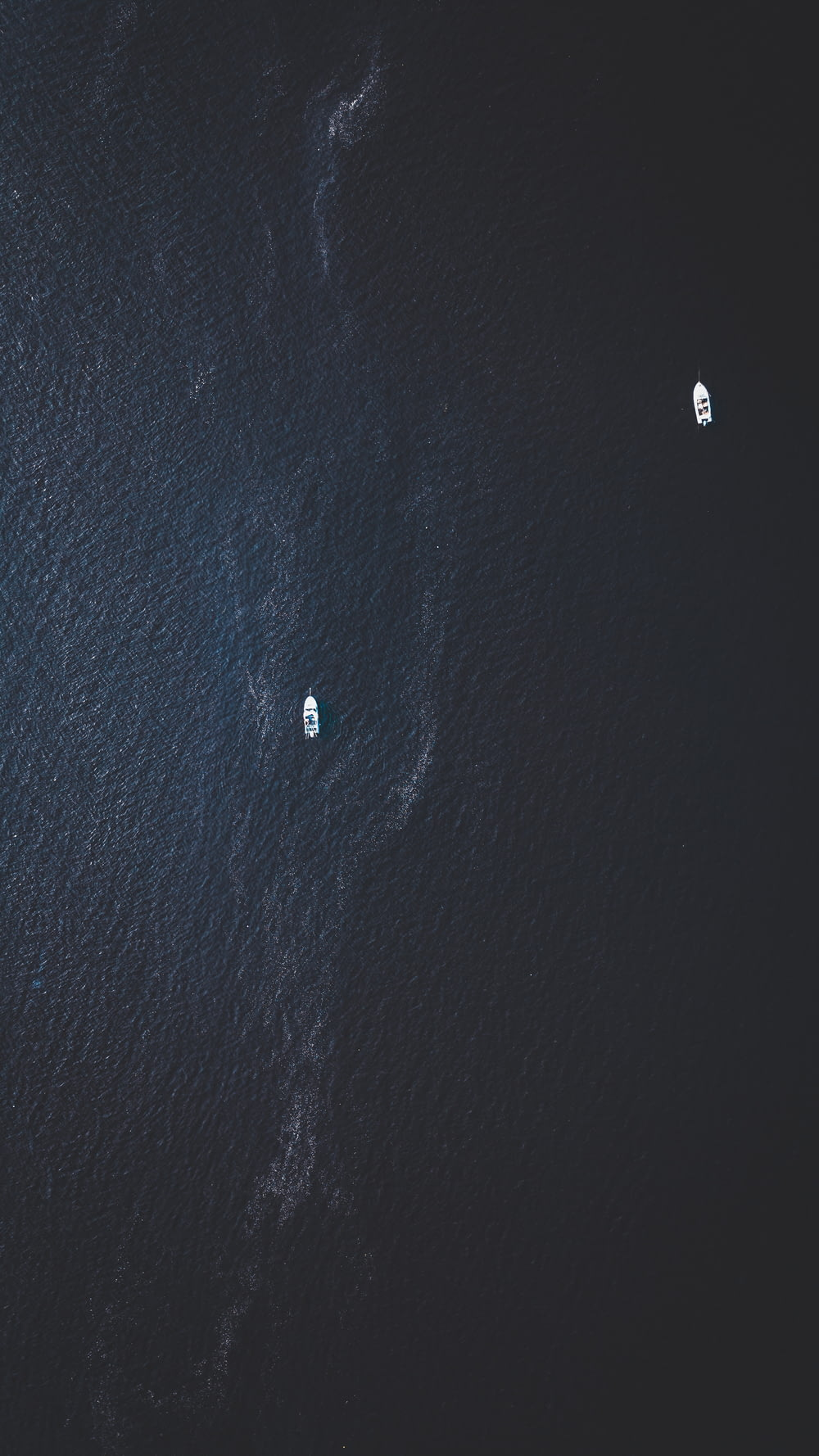 top view photography of two white boats on water at daytime