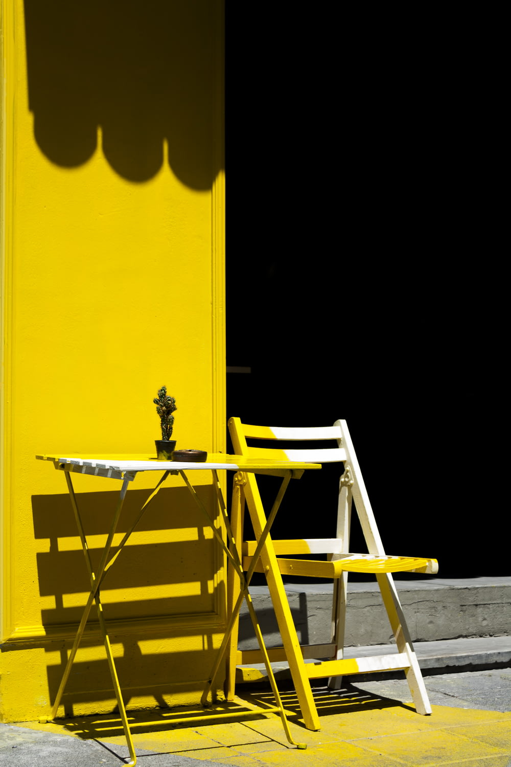 folding table and chair near yellow wall