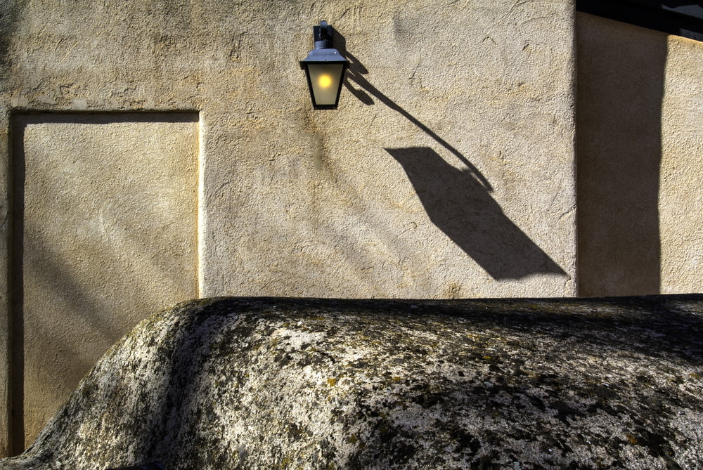 turned-on black outdoor sconce on wall at daytime