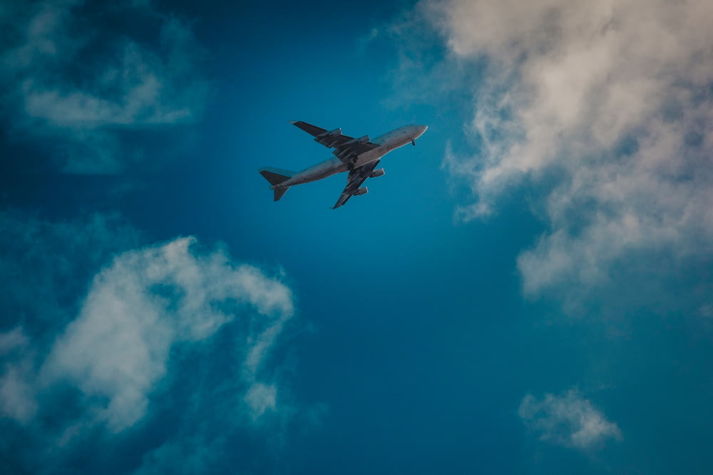 white airplane under blue and white cloudy sky