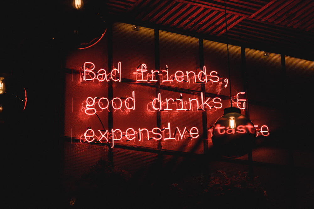 bad friends, good drinks & expensive taste neon sign on wall