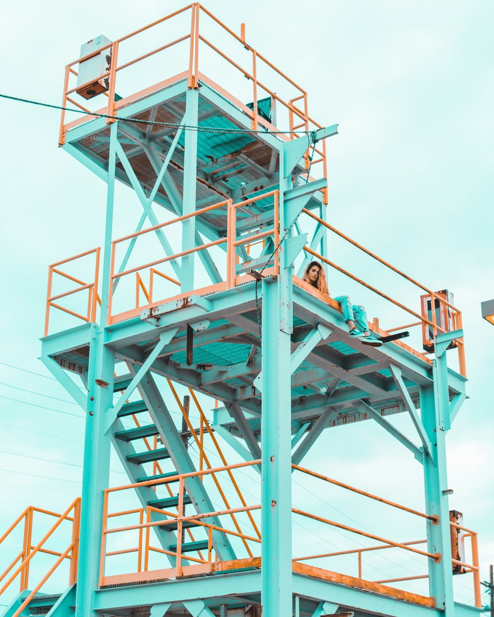 woman sitting on teal and yellow metal tower during daytime