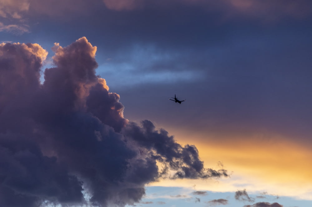 low-angle photography of plane near clouds