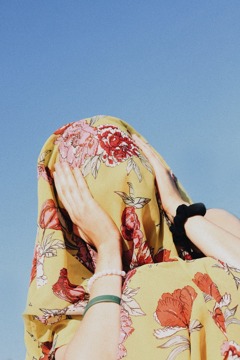 woman covering her face with yellow floral headdress