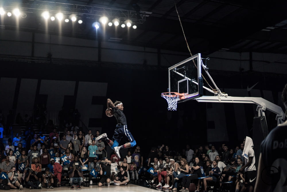 man jumping and about to shoot the ball in basketball hoop in front of crowd