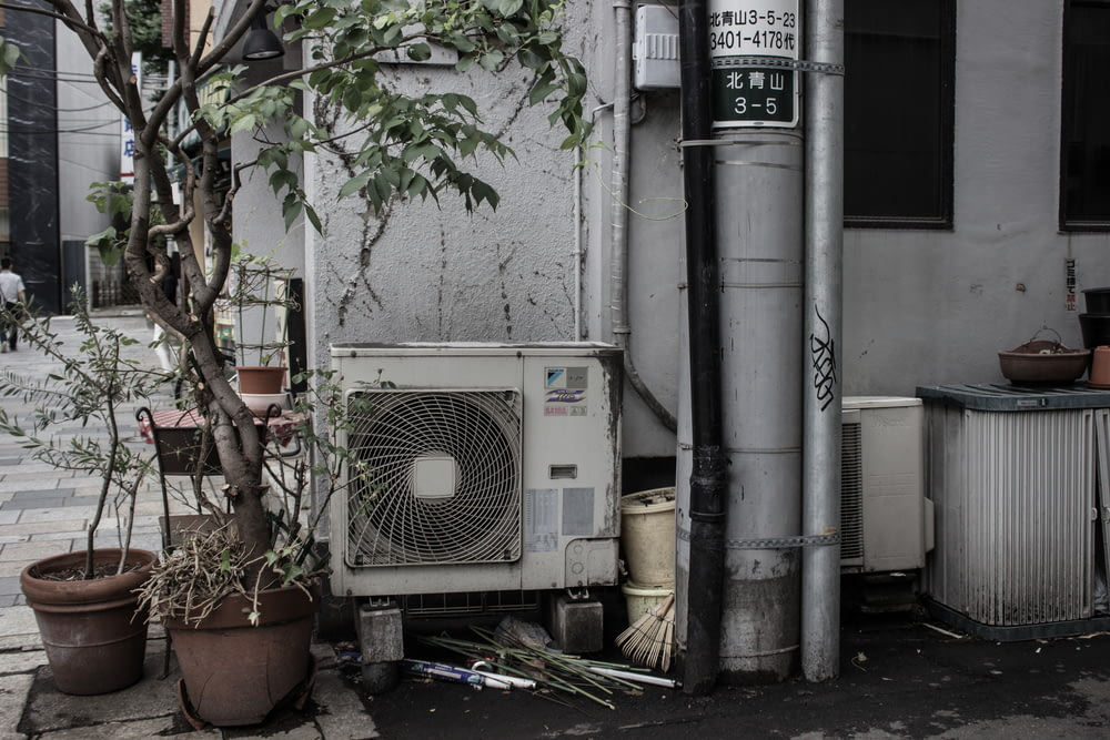 air condenser beside two potted plants outside building