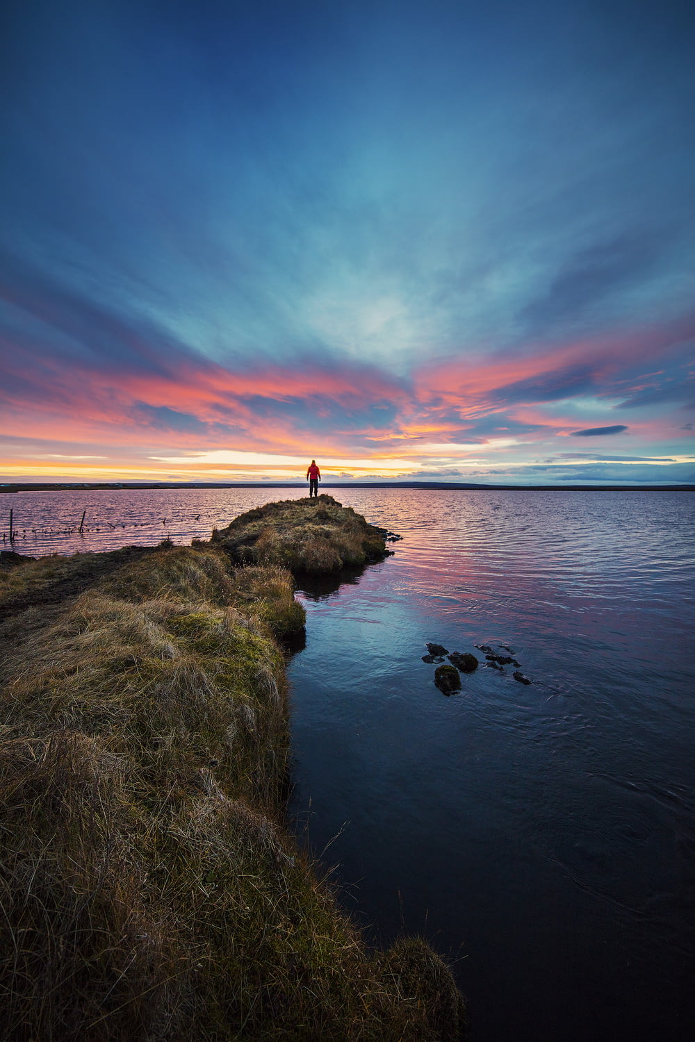 man stands on end of dike watching setting sun over sea