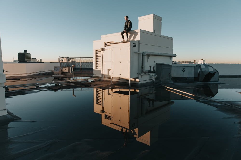 man sits on top of building