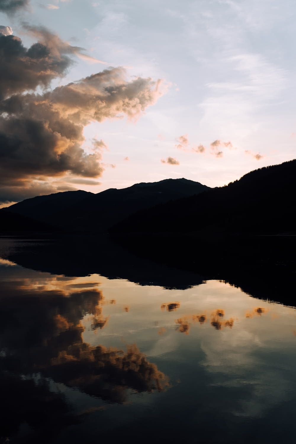 silhouette photography of mountain and body of water