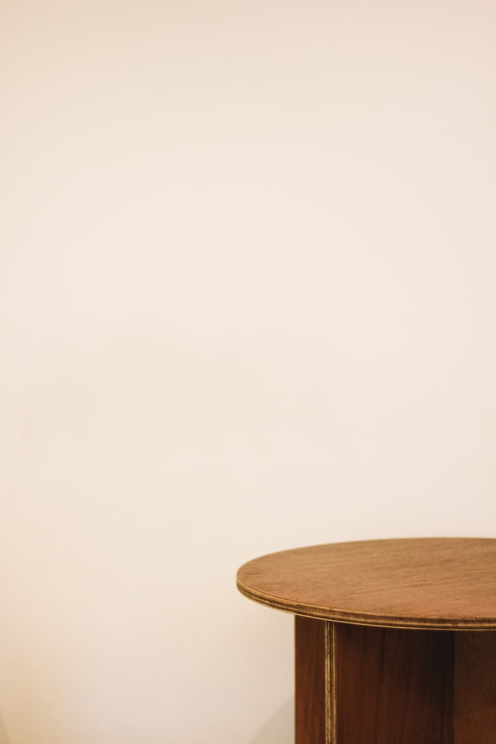 brown wooden end table beside white wall