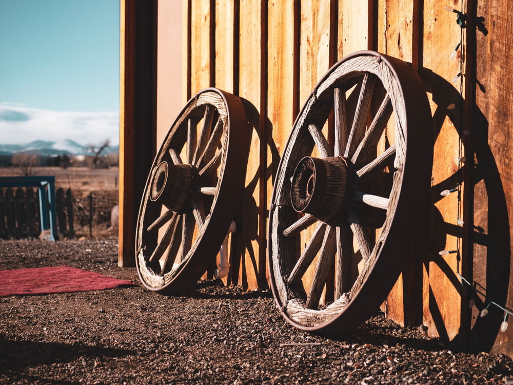 two brown carriage wheels learning on brown house