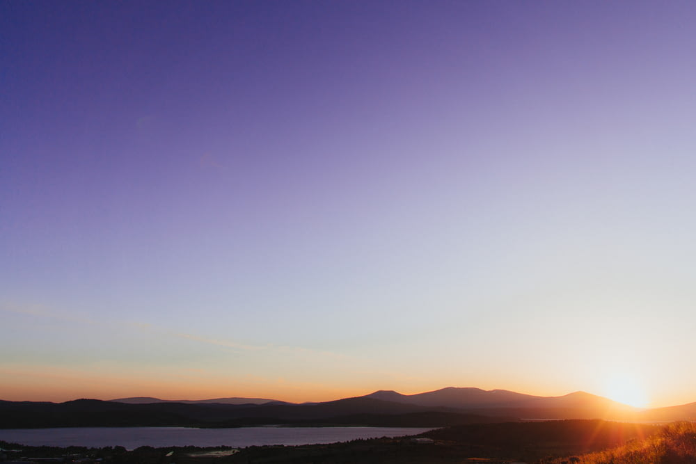 silhouette of mountains near body of water during orange sunset