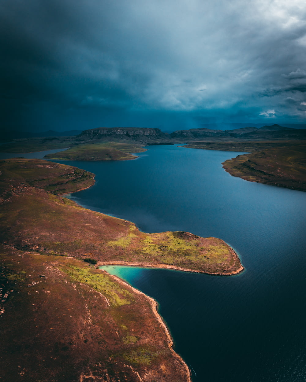 aerial photography of body of water with brown and green field under dramatic clouds