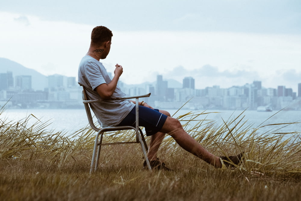 man sitting on armchair while overlooking high-rise buildings during daytime