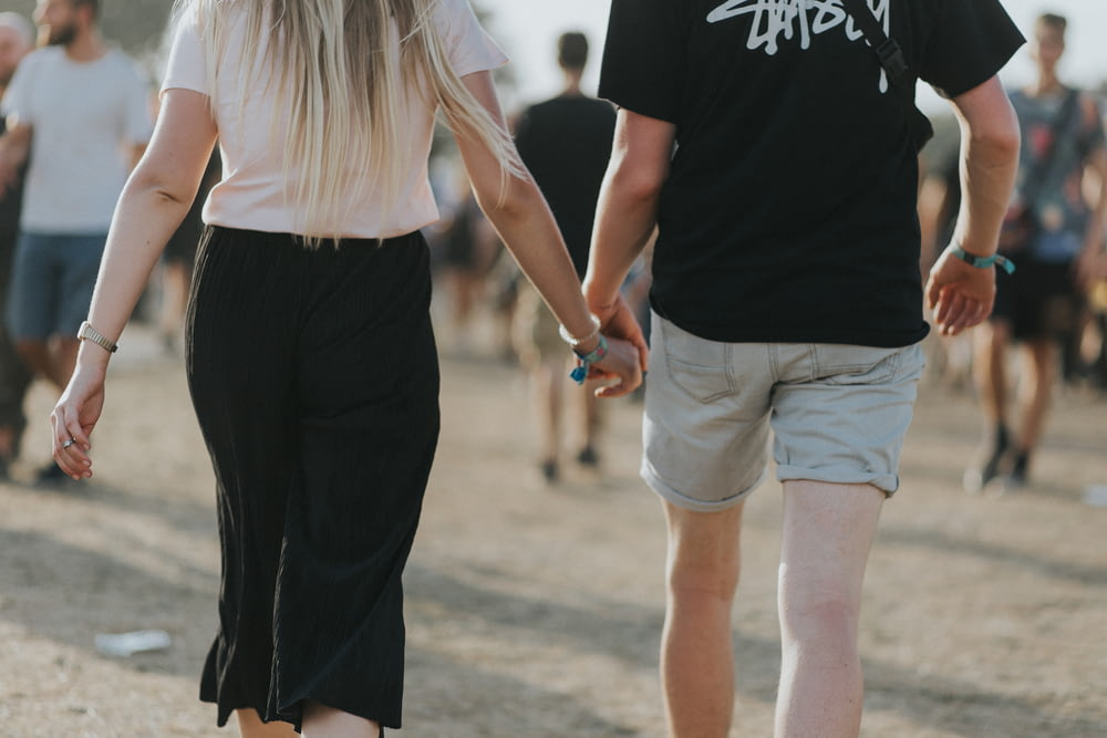 couple holding hands while walking