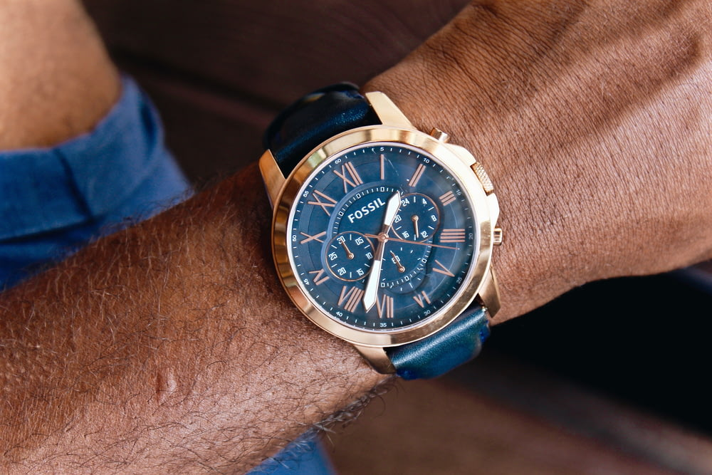 round gold-colored Fossil chronograph watch with leather band displaying 1:37 time