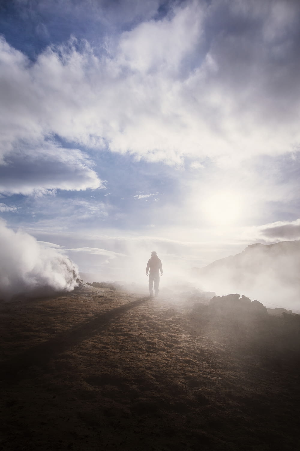person standing near the edge of a mountain near clouds during day