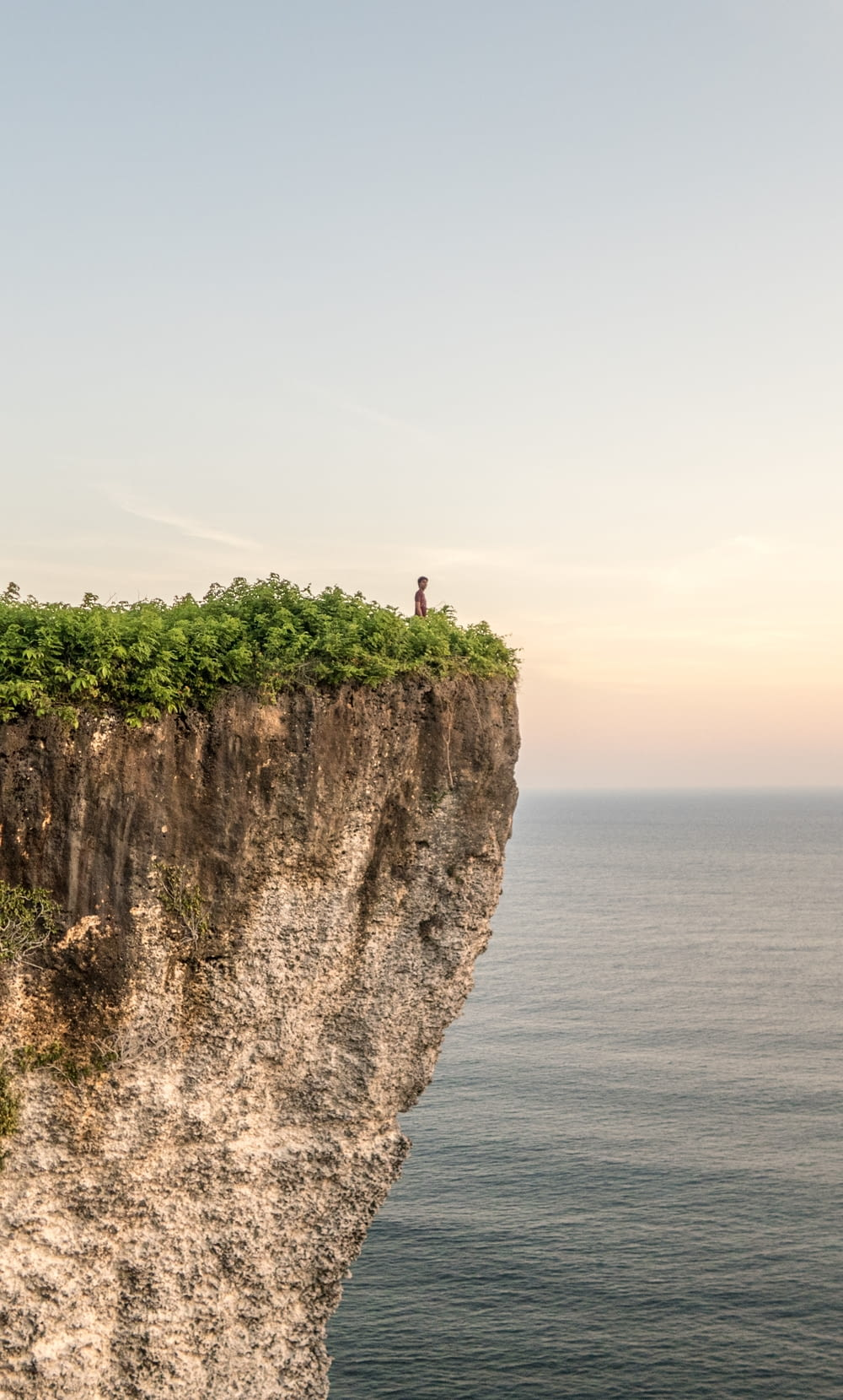 person standing on cliff during daytime