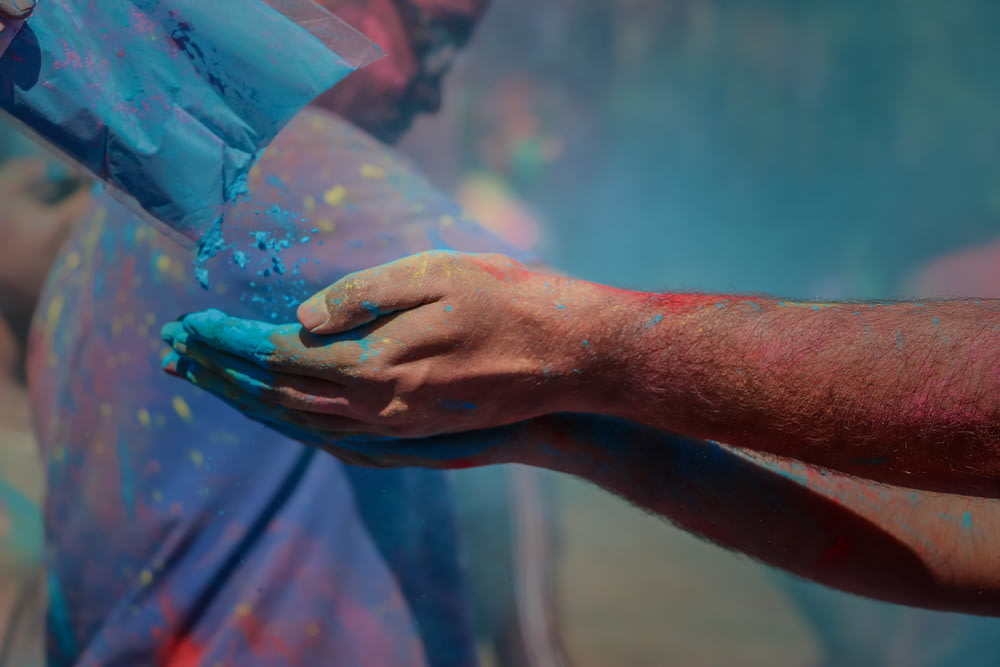 person catching blue powder