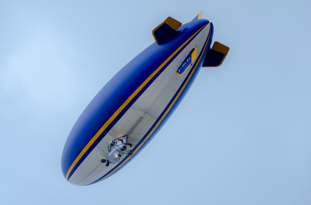 blue and white blimp flying under blue sky
