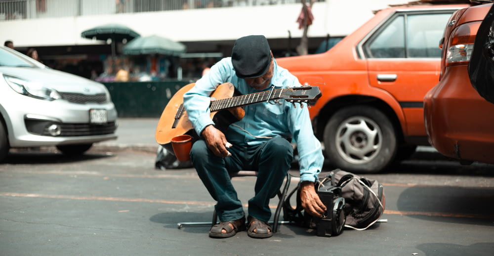 man sitting on street holding guitar