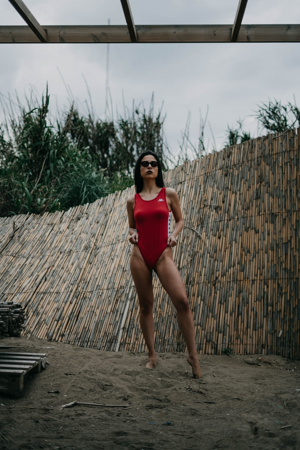 woman in red monokini standing while wearing black sunglasses