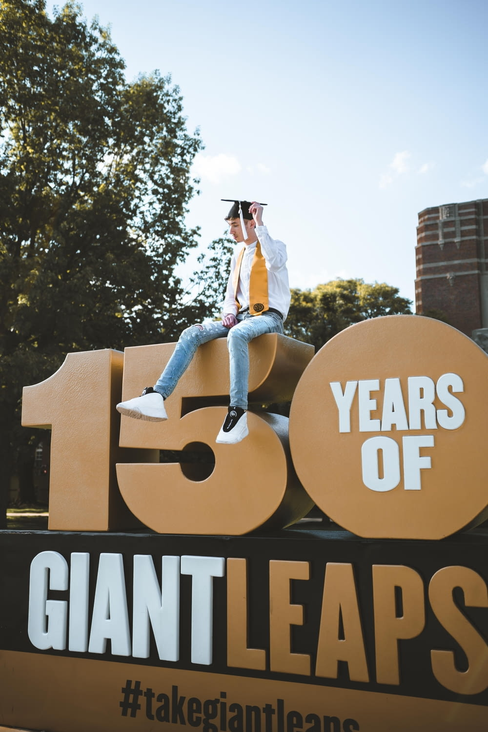 man with black mortar board sitting on 150 years giant leaps building