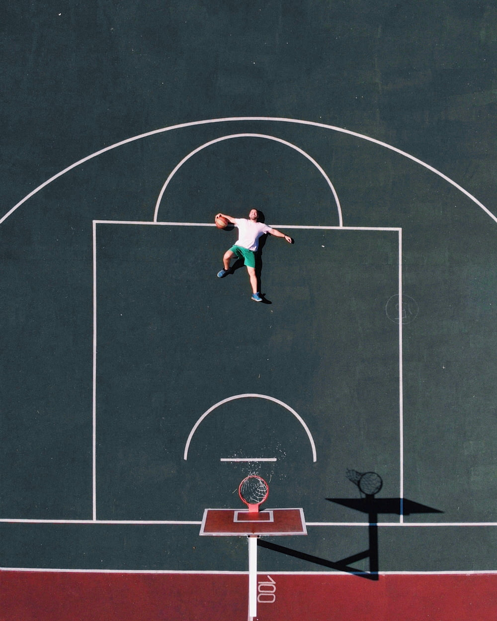 aerial photography of man lying on basketball court