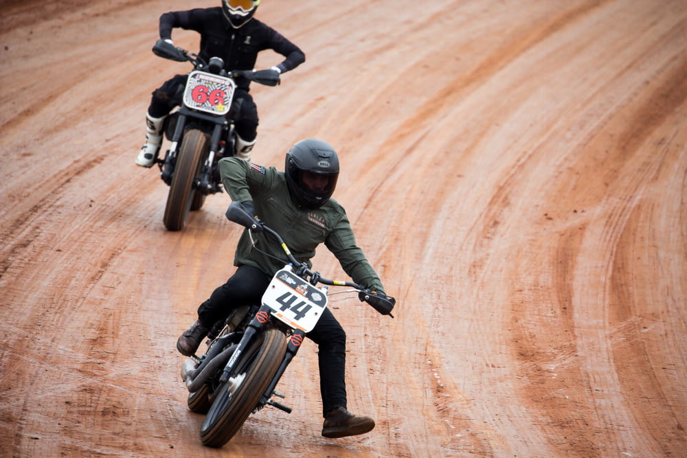 two men riding motocross on road