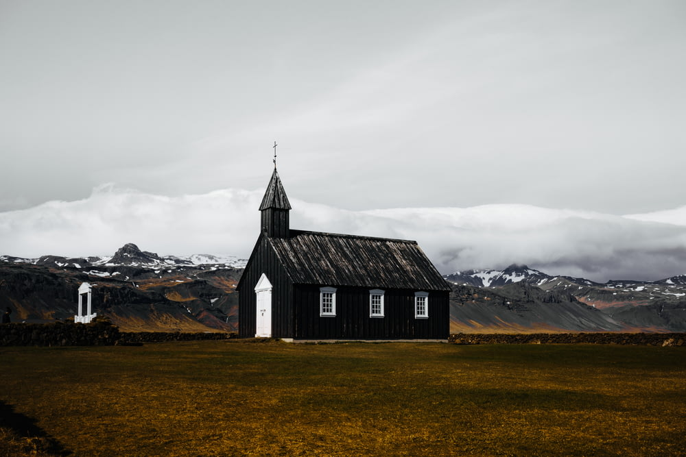 black and white wooden house in brown field