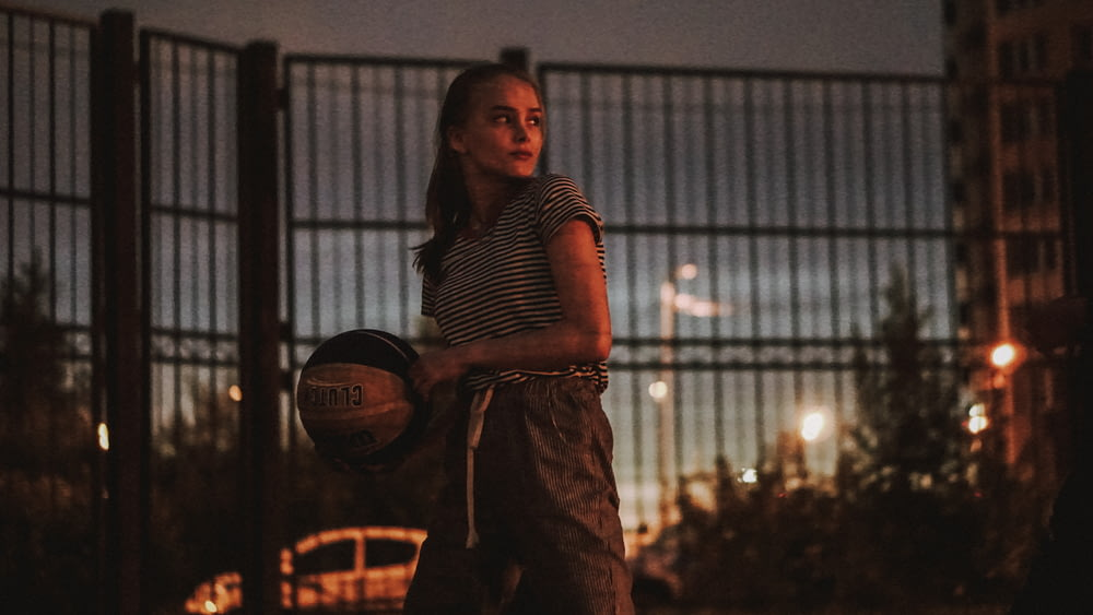 woman holding a black and white basketball ball