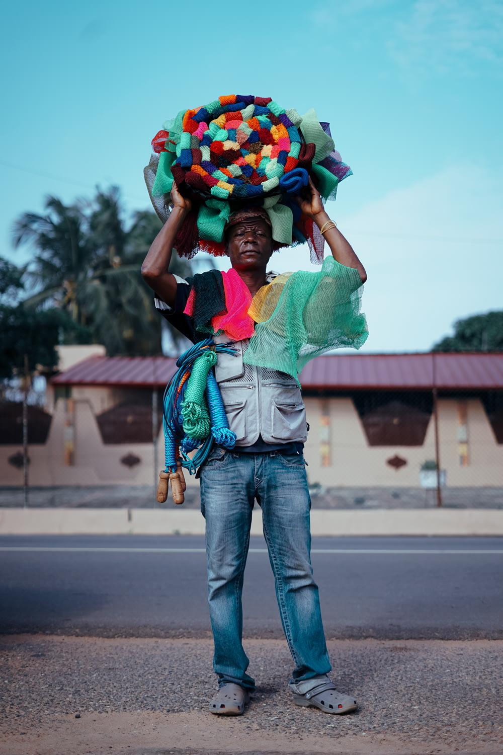 man standing and carrying multicolored hat