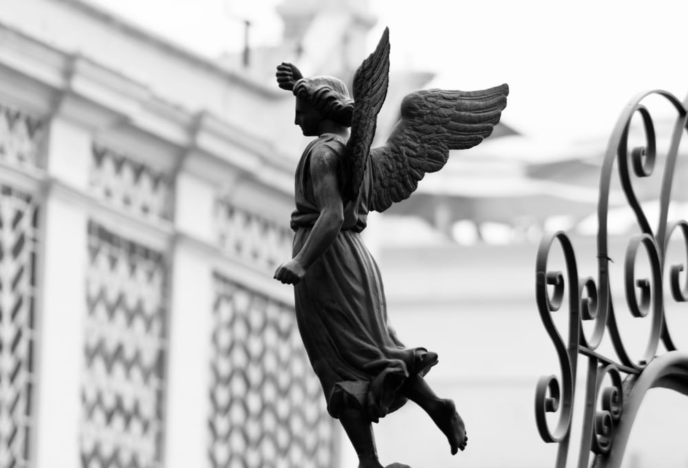 shallow focus photo of angel statue