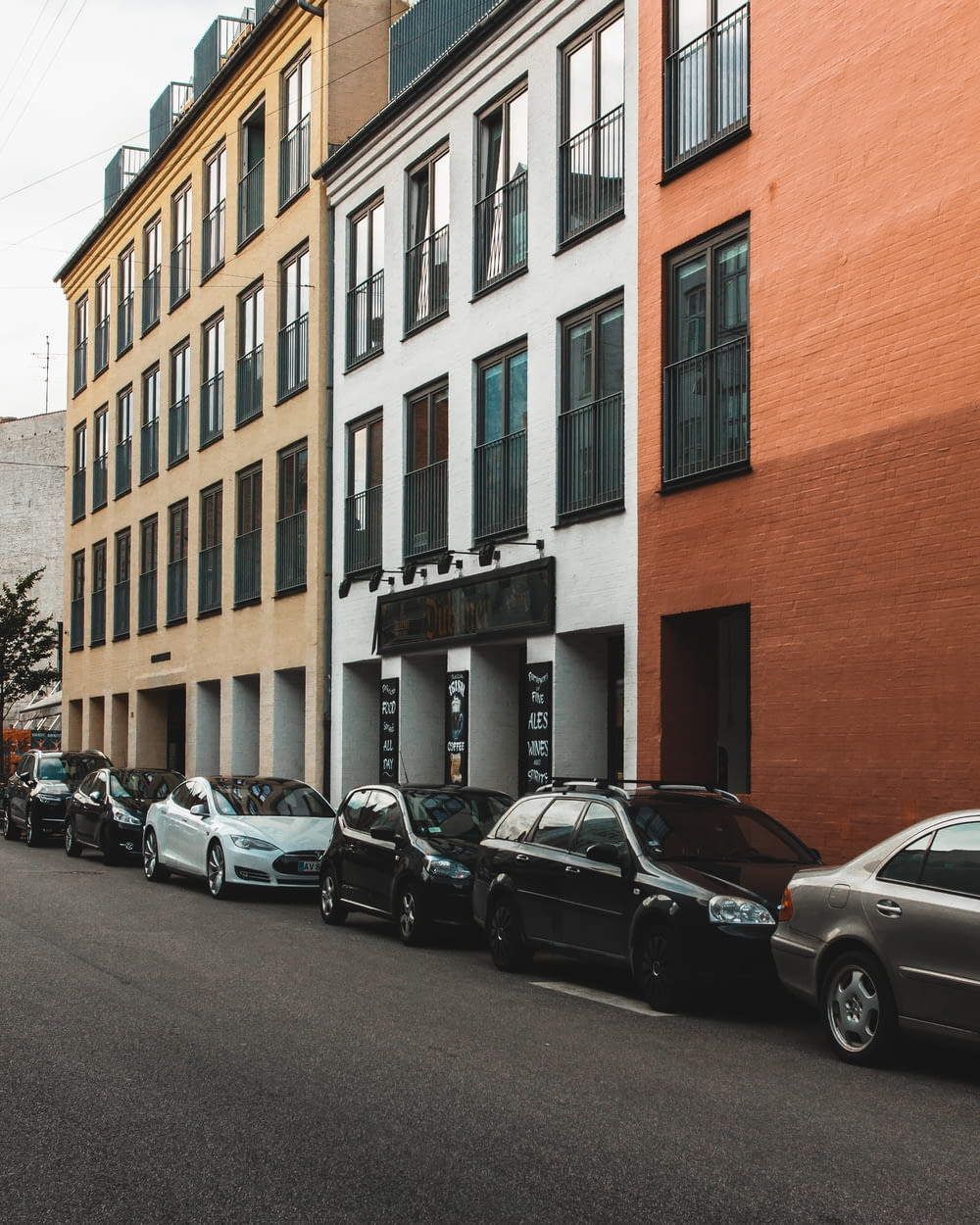 car lot parked beside buildings during daytime