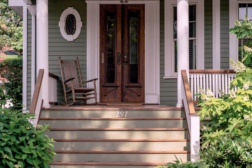 brown wooden rocking chair on porch beside closed French doors