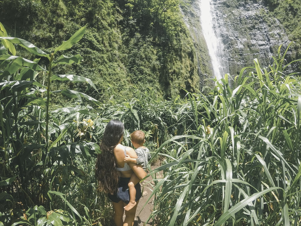woman holding baby walking on plant field front of waterfal