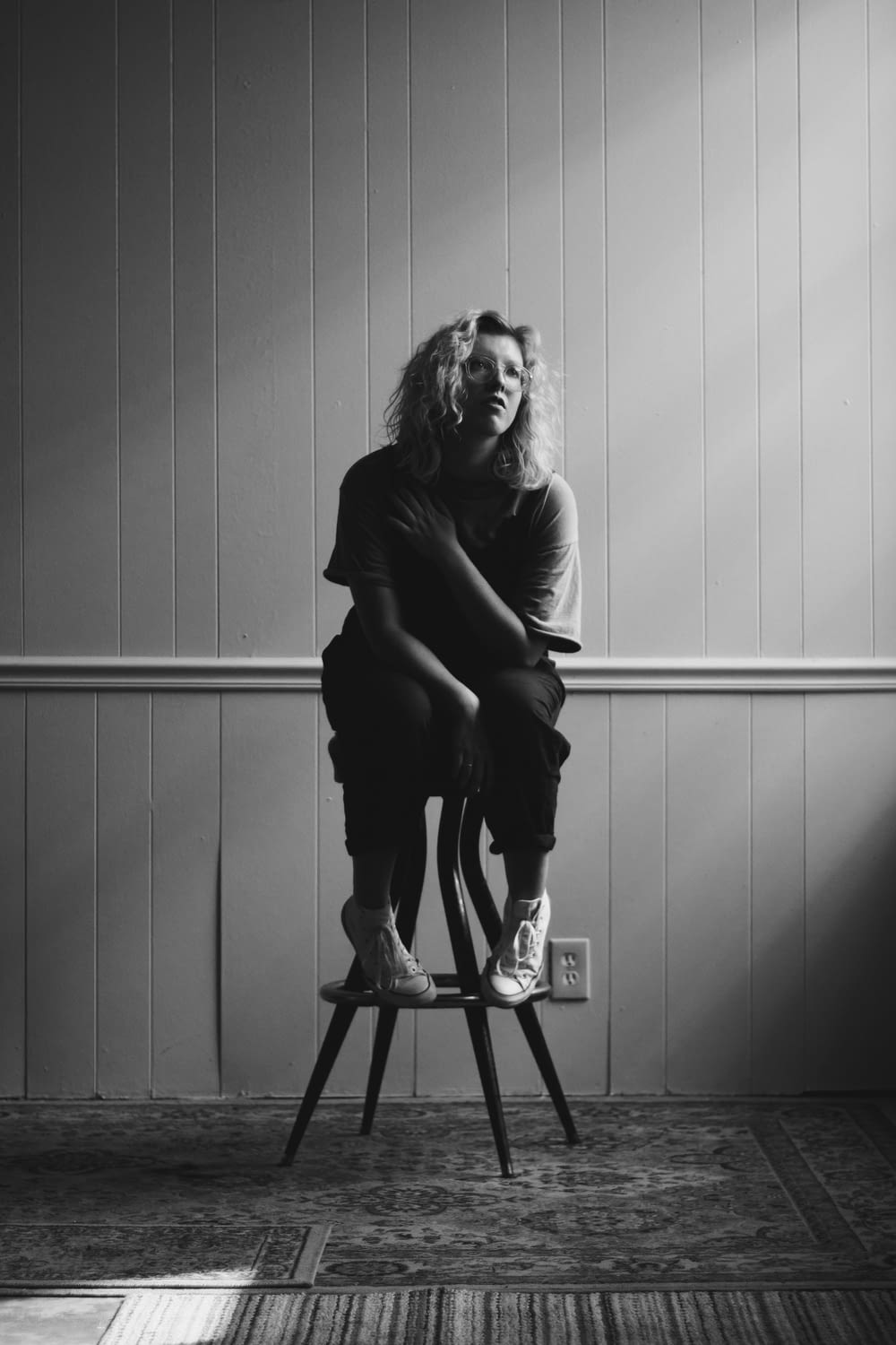 grayscale photography of woman sitting on chair