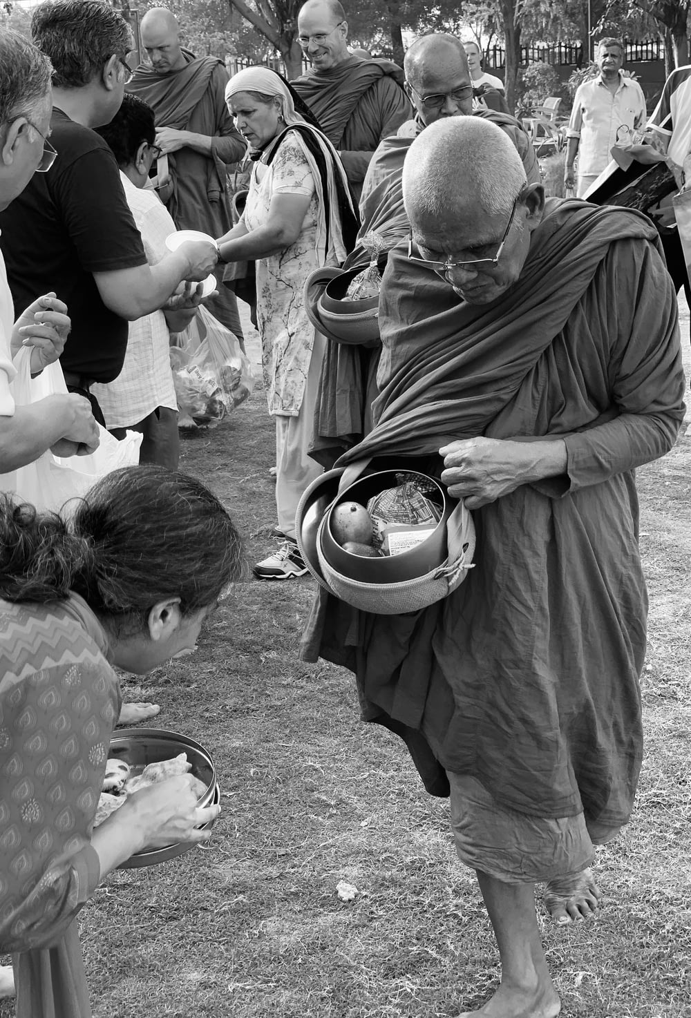 grayscale photo of man holding bowls beside woman