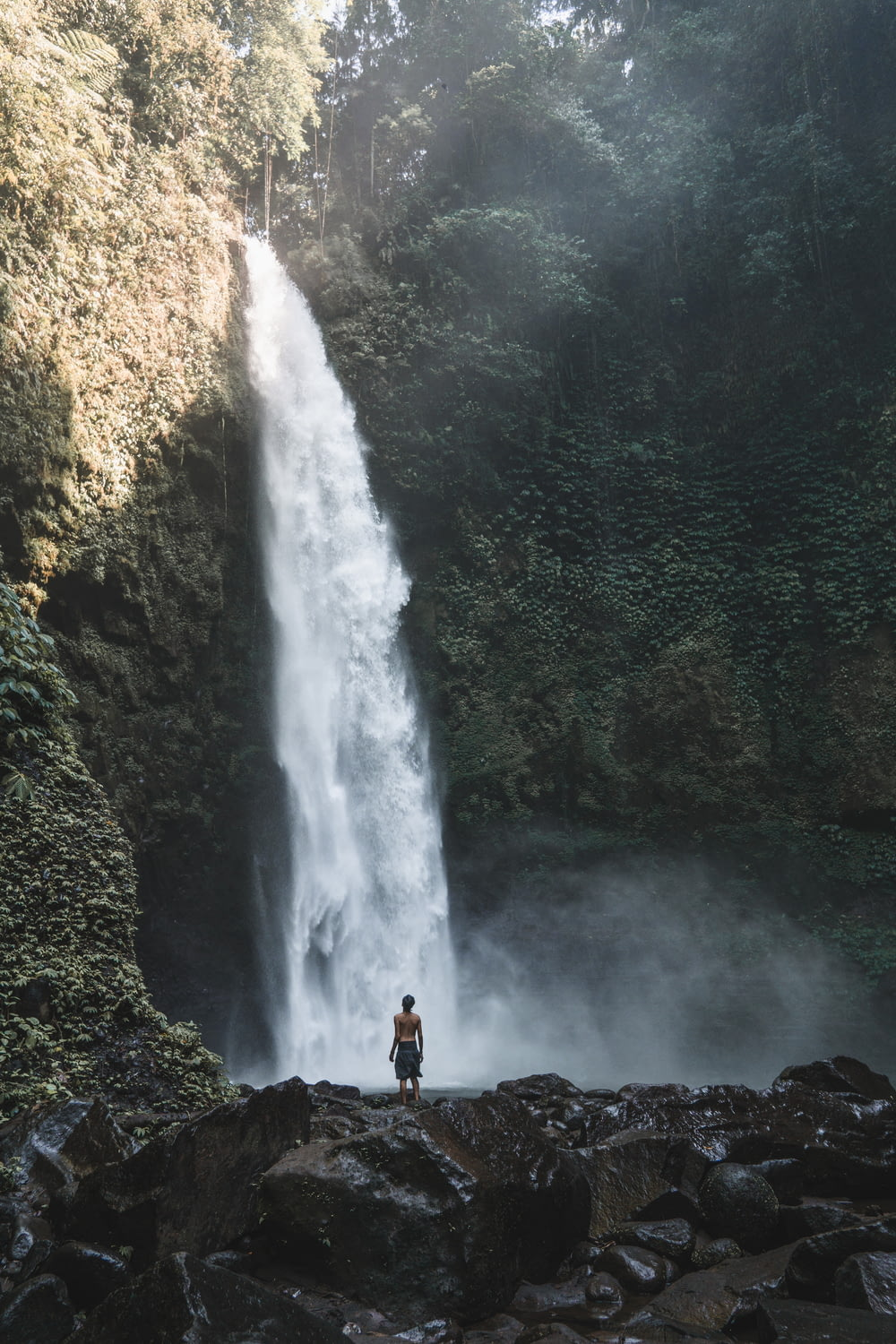man standing and facing the waterfalls during day