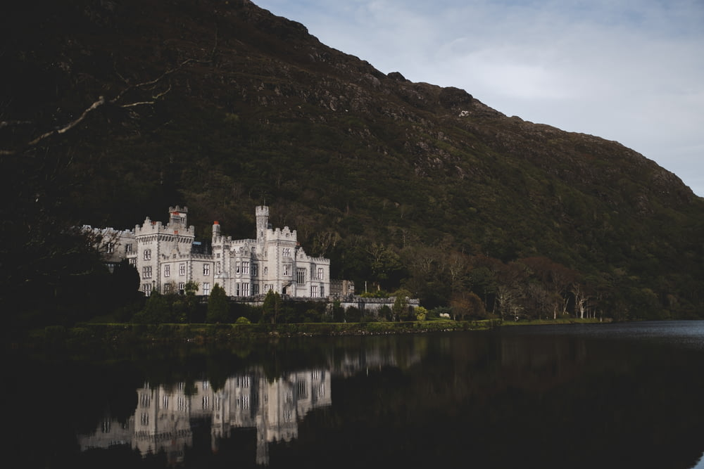 white castle beside mountain and body of water during daytime