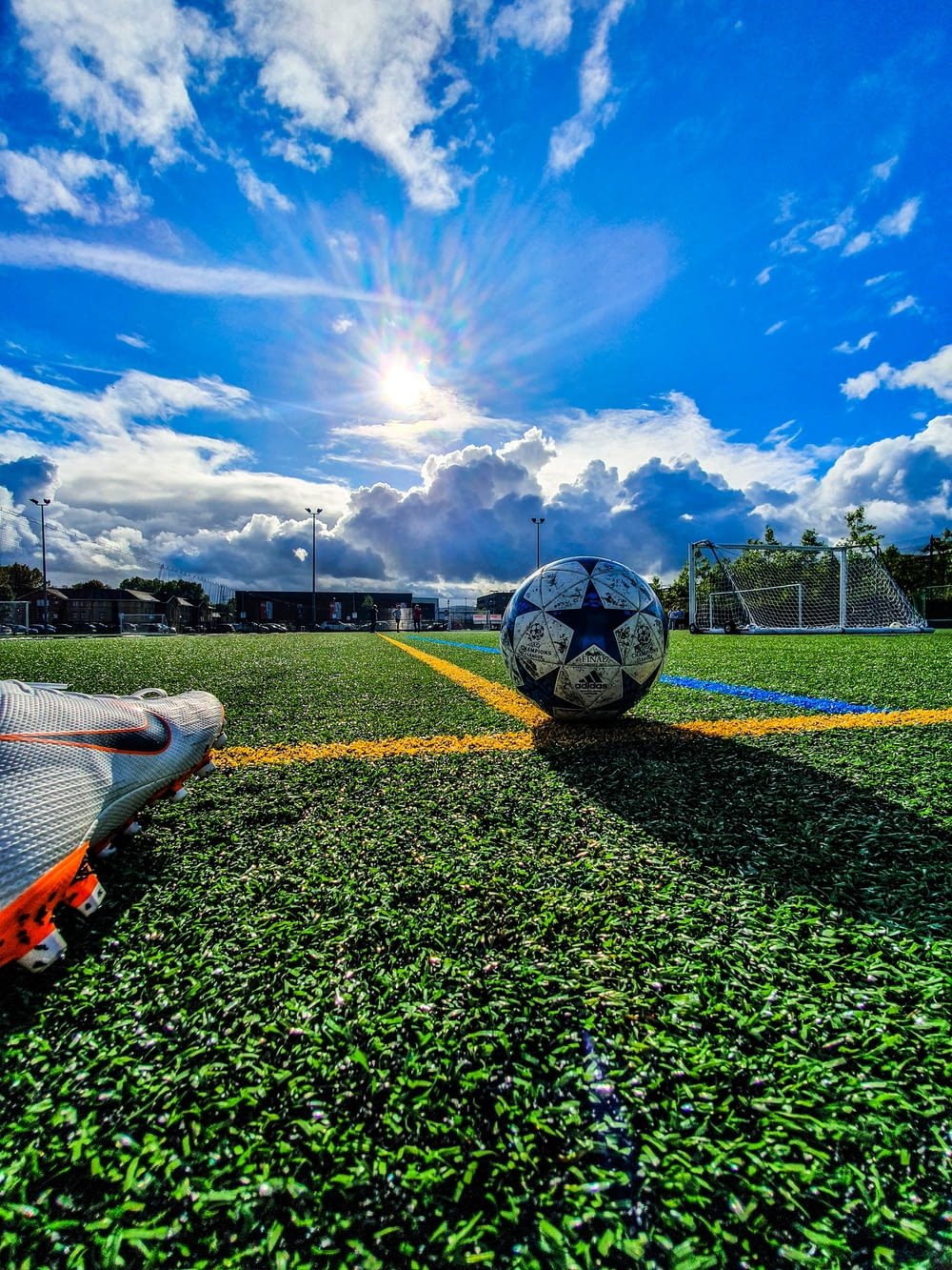blue and grey soccer ball on green field under white and blue sky during daytime